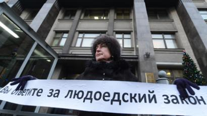 "A woman pickets outside the State Duma of the Russian Federation against the passage of the law prohibiting US citizens from adopting Russian children. ""You'll answer for the cannibal law,"" she wrote on her banner (RIA Novosti / Iliya Pitalev)"