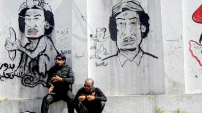 Libyan rebels in front of a wall covered in graffiti mocking Libya's leader Moamer Kadhafi (AFP Photo / Marwan Naamani)