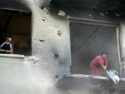 A South Ossetian woman cleans her destroyed flat in Tskhinval (AFP Photo / Kazbek Basayev)