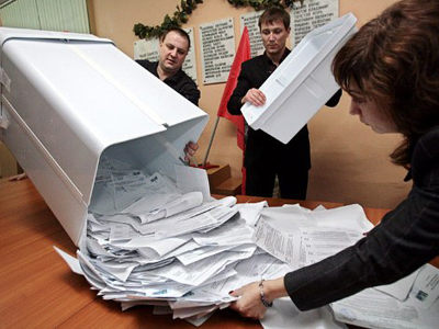 Members of a local voting commission empty a ballot box onto a table (AFP Photo / NATALIA KOLESNIKOVA)