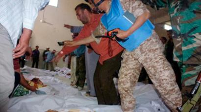 A member of the United Nations observers on a monitoring mission in Syria takes pictures of bodies of people whom anti-government protesters say were killed by government security forces, at Ali Bin Al Hussein mosque in Houla, near Homs in this handout dated May 26, 2012 (Reuters/Shaam News Network/Handout)
