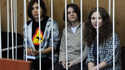 "Members of the all-girl punk band ""Pussy Riot"" Nadezhda Tolokonnikova (L), Maria Alyokhina (R) and Yekaterina Samutsevich (C), sit behind bars during a court hearing in Moscow on July 23, 2012. (AFP Photo/Andrey Smirnov)"