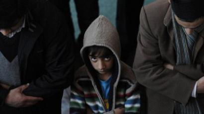 London: A boy looks up as he and other Muslims take part in Friday prayers in Baitul Futuh Mosque in south London, on February 18, 2011, as they attend a Unite Against Extremism call at Western Europe's largest mosque. (AFP PHOTO/CARL COURT)
