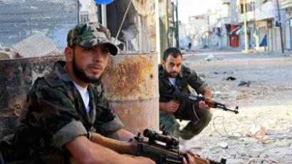 Free Syrian Army fighters patrol a street in Qusair town near Homs city, northern Syria May 5, 2012 (Reuters/Stringer)