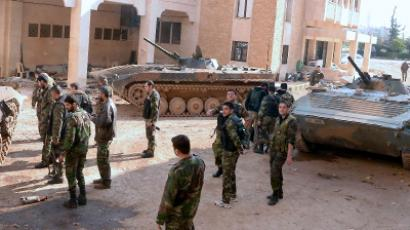 Syrian army soldiers stand by their armoured vehicles in the al-Layramun district of the northern city of Aleppo, which is under government troops control, on November 26, 2012. (AFP Photo)