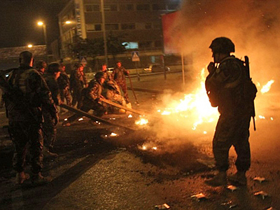 Lebanese soldiers try to extinguish flames from burning tires set ablaze by protesters in Beirut, on January 24, 2011 (AFP Photo / Anwar Amro)