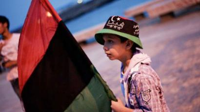A Libyan boy holds a former Libyan flag as he plays along the sea promenade on June 2, 2011 in the eastern rebel held city of Benghazi (AFP Photo / Gianluigi Guercia)