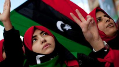 Libyan women wear pre-Gaddafi flags as they protest to demand the resignation of Libyan leader Moammar Gaddafi during a demonstration in Benghazi, eastern Libya