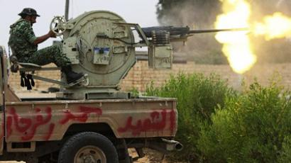 A Libyan National Transitional Council (NTC) fighter fires with a heavy machine gun during a battle in the streets of Sirte on October 7, 2011 (AFP Photo / Ahmad Al-Rubaye)