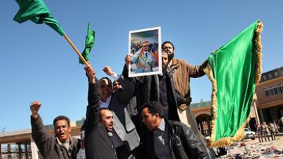 Muammar Gaddafi supporters pose with pictures of the Libyan leader in a no-mans-land between the two countries on March 02, 2011 in Ras Jdir, Tunisia- Libya border