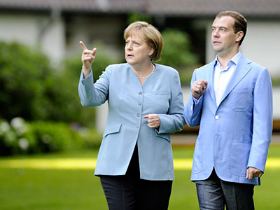 Russian President Dmitry Medvedev (R) and German Chancellor Angela Merkel walk through a garden before their meeting during the German-Russian consultations in Hanover July 18, 2011 (AFP Photo / Getty Images)