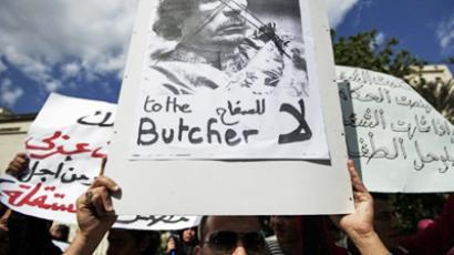 Egyptian and Libyan protesters shot slogans against Libyan leader Moamer Kadhafi (portrait) during a demonstration outside the Arab League headquarters in the Egyptian capital Cairo on February 21, 2011 (AFP Photo / Gianluigi Guercia)