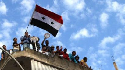 Syrian regime supporters wave the Syrian flag during a protest in the Nabaa neighborhood of Beirut  (AFP Photo / ANWAR AMRO)