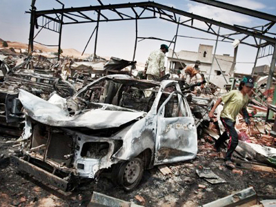 Libyans inspect the damage at a factory targeted by NATO air strikes in Bir Ghanam on August (AFP Photo / Colin Summers)