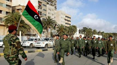A Libyan rebel waves his country's former flag, now used by the rebellion, during a parade along a seaside promenade in their stronghold of Benghazi on April 27, 2011 (AFP Photo / Getty Images)