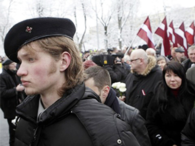 People wait to put flowers at the Freedoms monument during procession commemorating the Latvian Waffen SS unit, also known as the Legionnaires, in Riga March 16, 2010