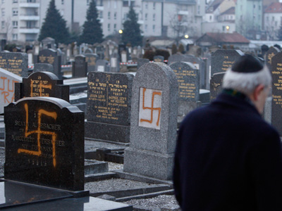 Francis Levy, head of the North Alsacian Jewish community, inspects desecrated tombstone in the Jewish Cemetary of Cronenbourg near Strasbourg. (REUTERS/Vincent Kessler)