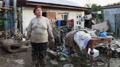 A woman stands in a courtyard of her house, hit by floods, in the town of Krymsk in Krasnodar region, southern Russia, July 8, 2012. (Reuters/Eduard Korniyenko)