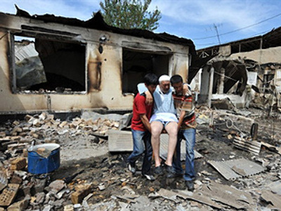 Kyrgyzstan, Osh : People help an elderly ethnic Uzbek man in front of his burnt-out house in Osh on June 15, 2010. (AFP Photo / Viktor Drachev)
