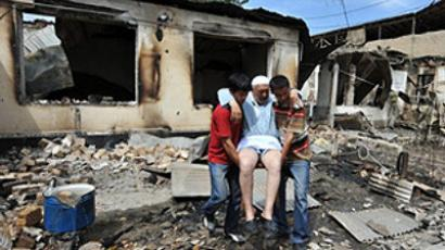 Kyrgyzstan, Osh : People help an elderly ethnic Uzbek man in front of his burnt-out house in Osh on June 15, 2010. (AFP Photo / Viktor