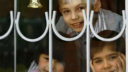 Orphan children look out from a window. (Reuters)
