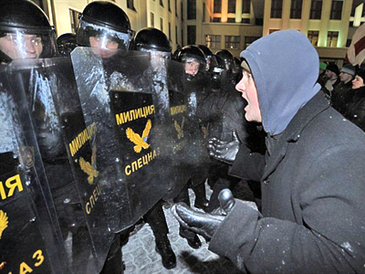 A protester gestures towards riot police during an opposition rally in Minsk early on December 20, 2010. (AFP Photo / Victor Drachev)