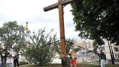 Activists of the Ukrainian feminist group Femen use a chainsaw to cut down a cross, erected to the memory of victims of the political repression in Kiev on August 17, 2012 in support of Russian punk group Pussy Riot. (AFP Photo/Genya Savilov)