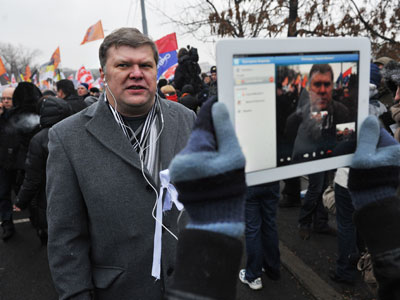 "Co-chairman of the Yabloko party Sergei Mitrokhin recording an interview among participants in the rally ""For Fair Elections"" on Bolotnaya Square (RIA Novosti / Artyom Zhitenev)"