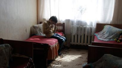 A boy sits in his room at a boarding school for the visually and hearing impaired children in a settlement in Meshyovsk, 250 km (155 miles) outside Moscow.(Reuters / Alexander Natruskin)