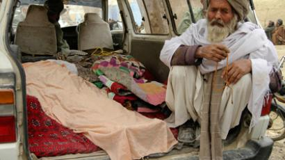 An elderly Afghan man sits next to the covered bodies of people who were killed by coalition forces in Kandahar province, March 11, 2012 (Reuters / Ahmad Nadeem)