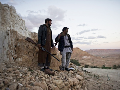 Libyan anti-government fighters stand on a mountain near Nalut