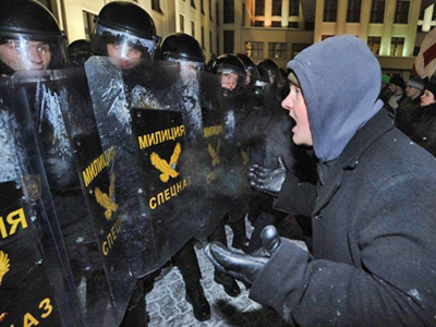 Belarus, Minsk : A protester gestures towards riot police during an opposition rally in Minsk. (AFP Photo / Viktor Drachev)