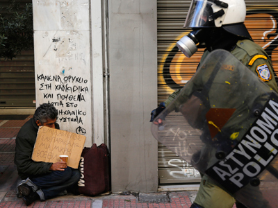 Riot policeman walks by a homeless beggar during a rally to mark the 2008 shooting of a student by police in Athens' Syntagma (Constitution) Square, December 6, 2012 Reuters / Yannis Behrakis