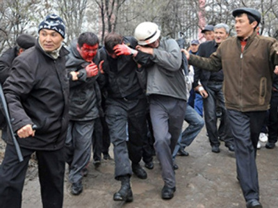 Blooded Kyrgyz police officers are held by opposition supporter during an anti-gove