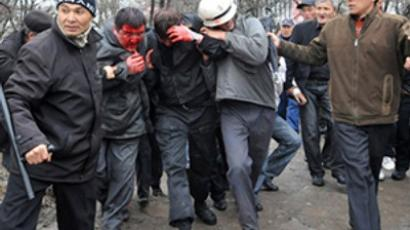 Blooded Kyrgyz police officers are held by opposition supporter during an anti-government protest in Bishkek on April 7, 2010 (AFP Photo / Vyacheslav Oseledko)