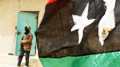 A rebel fighter stands guard behind a Kingdom of Libya flag at Dehiba, at the border crossing between southern Libya and Tunisia April 23, 2011 (AFP Photo / Joseph Eid)