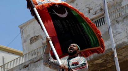 A Libyan man shouts slogans as he waves the flag of the Libyan revolution (AFP Photo / Saeed Khan)