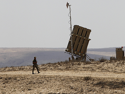 An Israeli soldier walks next to a rocket shield system launcher near Beersheba. (Reuters / Baz Ratner)