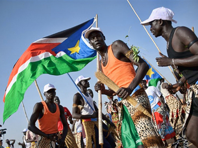Sudan, Juba: A group of southern Sudanese men wave local flags and dance outside a polling station in Juba during on January 9, 2011. (AFP Photo / Phil Moore)