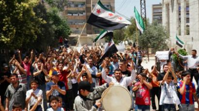 Anti-government protesters clap their hands as part of a funeral procession for Yaser Raqieh, whom protesters say was killed by forces loyal to Syria's President Bashar al-Assad, near Hama June 5, 2012 (Reuters/Handout)