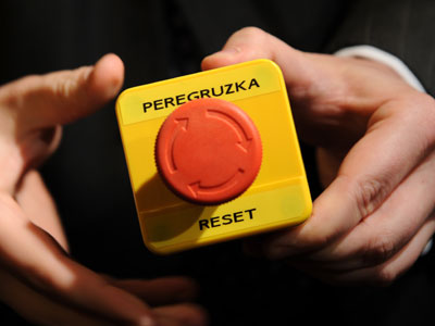 "An assistant shows the block with a red button marked ""reset"" in English and ""overload"" in Russian that US Secretary of State Hillary Clinton handed to Russian Foreign Minister Sergei Lavrov during a meeting on March 6, 2009 in Geneva.(AFP Photo / Fabrice Coffrini)"
