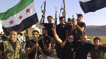 Members of Free Syrian Army fighters holding their weapons and opposition flags are pictured at Sermada near Idlib. (Reuters)