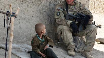 Afghan boy finds a friend (U.S. Army photo by Spc. Kristina Truluck, 55th Signal Company)