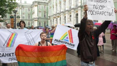 "A Russian gay rights activist holds a banner reading ""Homophobia - disgrace of a country"" during the gay pride protest, near the Hermitage Museum, in Saint Petersburg on June 26, 2010. (AFP Photo/Kirill Kudriavtsev)"
