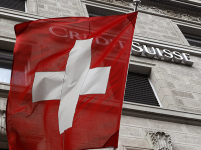 A Switzerland national flag flies in front of the logo of Swiss bank Credit Suisse at a branch office in Zurich (Reuters/Arnd Wiegmann)