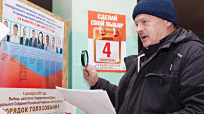 Man with a child drops a ballot into an automated ballot box to vote at polling station №332 in Yuzhno-Sakhalinsk. (RIA Novosti /Sergey Krasnouhov)