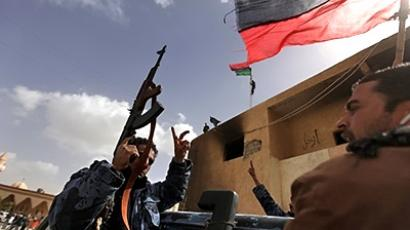Tobruk : Members of Libya's internal security forces wave their old national flag as they parade in the eastern city of Tobruk on February 24, 2011. (AFP Photo)
