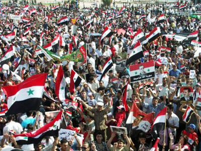 A photo released by the Syrian Arab News Agency (SANA) shows thousands of Syrians waving national flags and pictures of Syria's President Bashar al-Assad during a rally on June 16, 2011 (AFP Photo / HO / SANA)