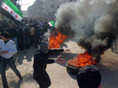 Syrian protesters burning tires and waving independence flags during an anti-regime demonstration on February 4, 2012 (AFP Photo / HO / LCC Syria)