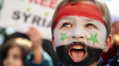 Amongst the protests in Syria, a boy is painted in the colors of the Syrian flag (AFP Photo / Ben Stansall)